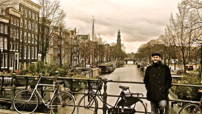 man leaning on bridge railing amsterdam