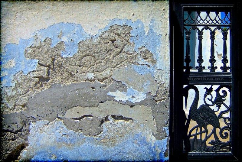 weathered wall and iron gate santorini greece